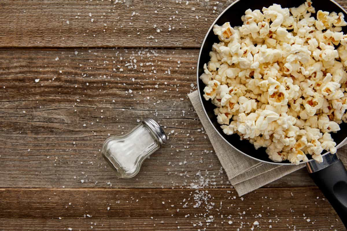top view of delicious popcorn in frying pan near scattered salt on wooden background, 10 Types Of Oil For Popcorn To Consider