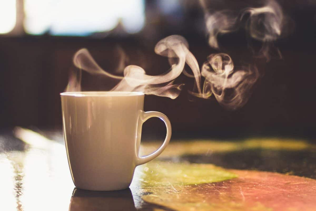 A cup of steaming milk on the table