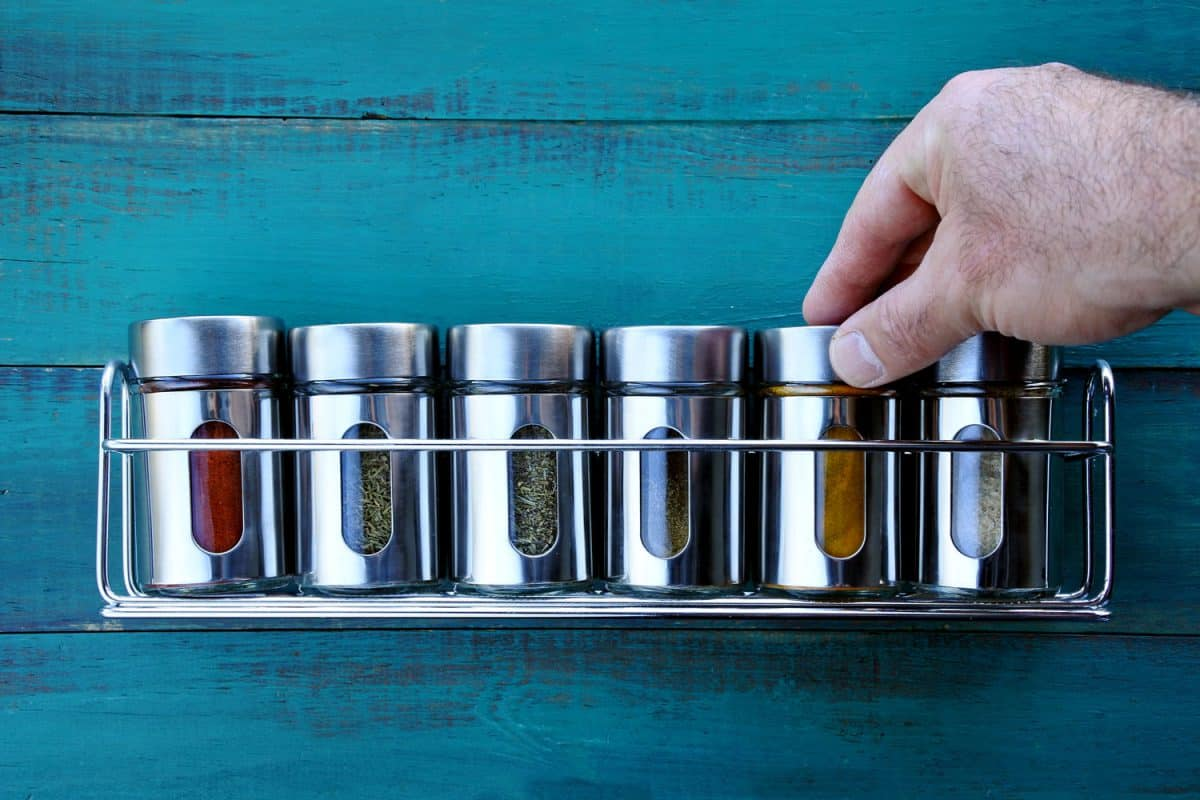 A man arranging his spices in small stainless containers