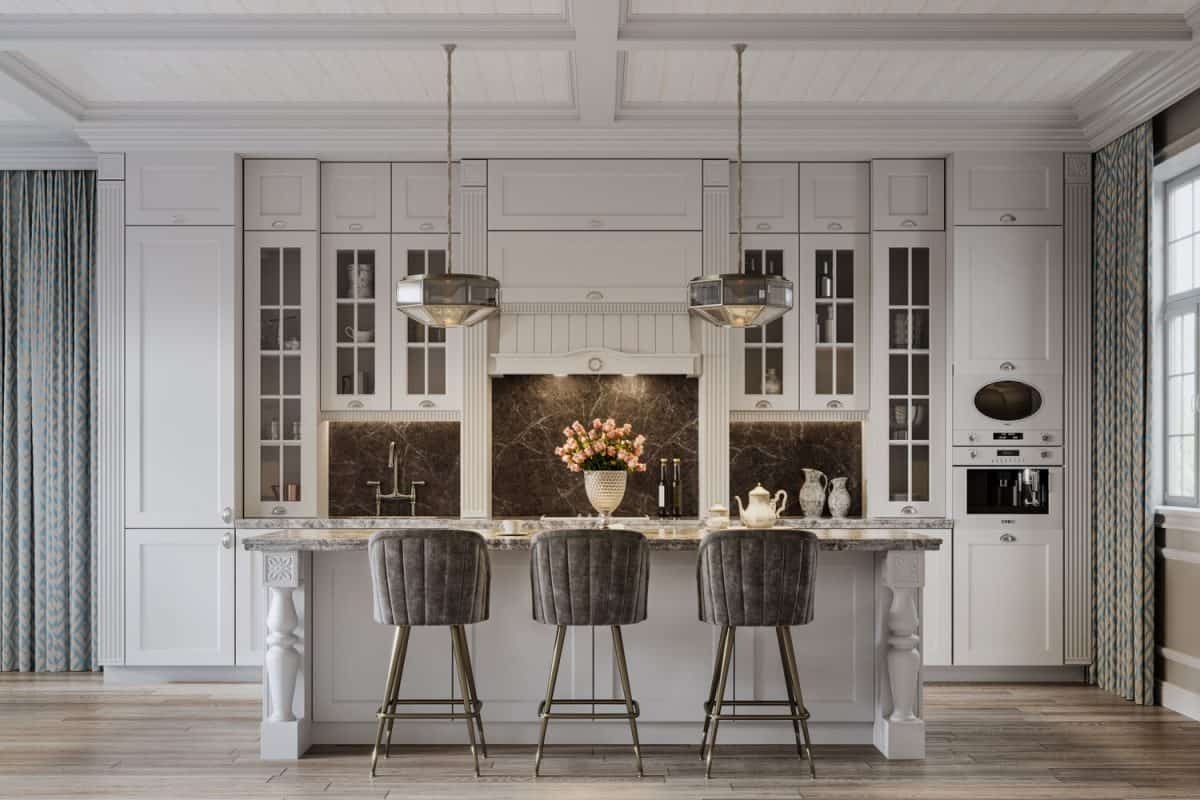 A mid century inspired kitchen with light gray cabinetries hanging lamps and a rustic breakfast bar