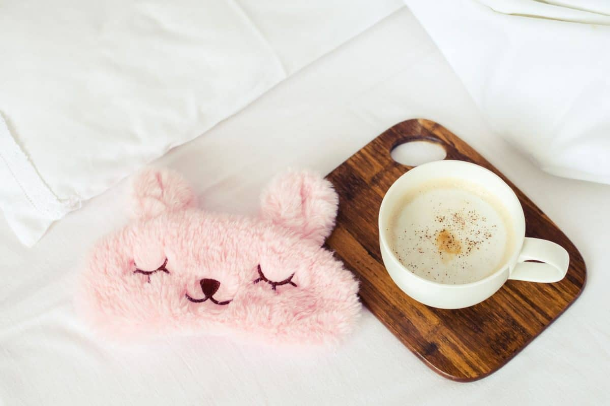 A wooden coaster with a cup of milk and a small teddy bear eye patch