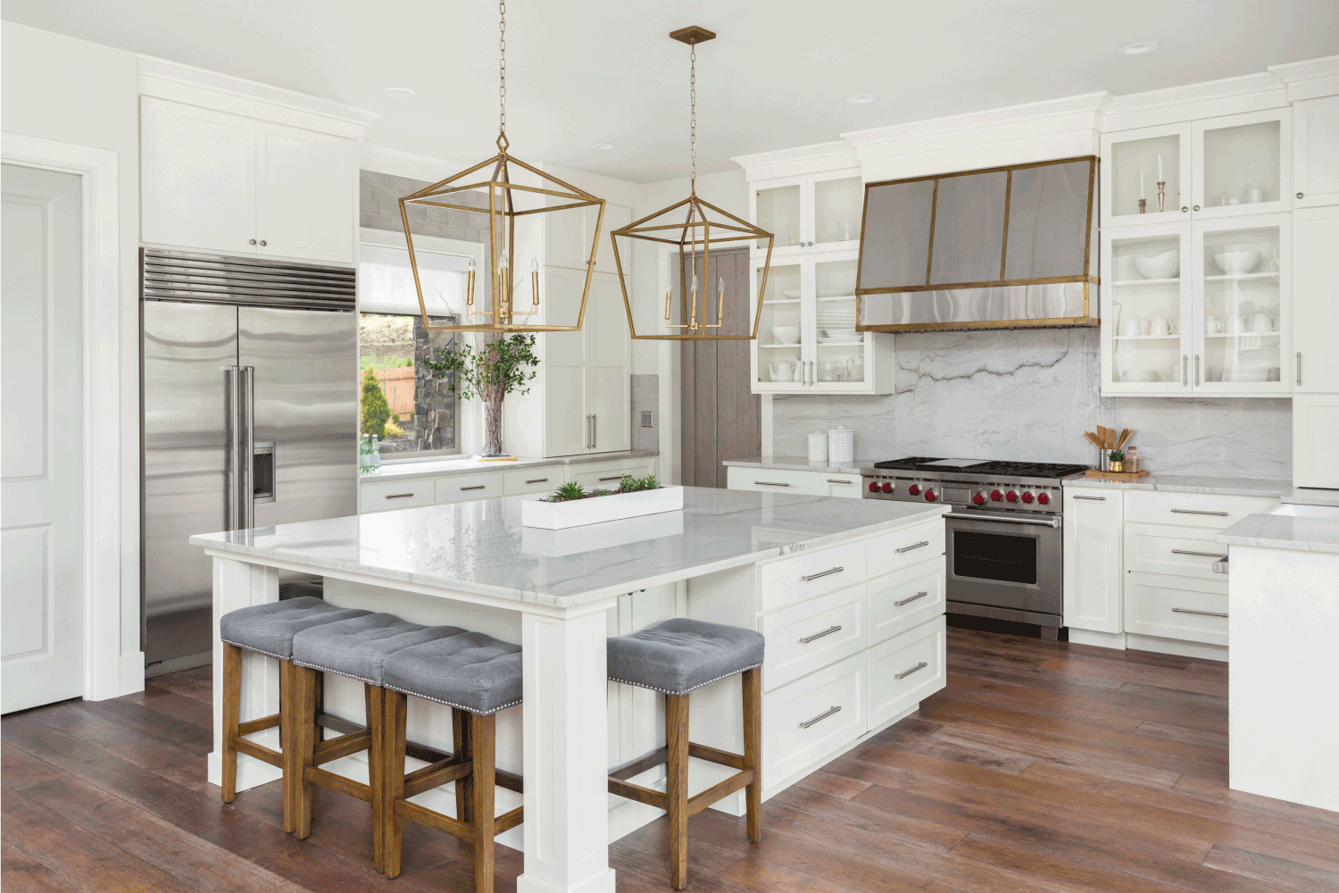 Beautiful kitchen in new luxury home with island, pendant lights, and hardwood floors. Should Kitchen Floor Match Worktop Or Cabinets
