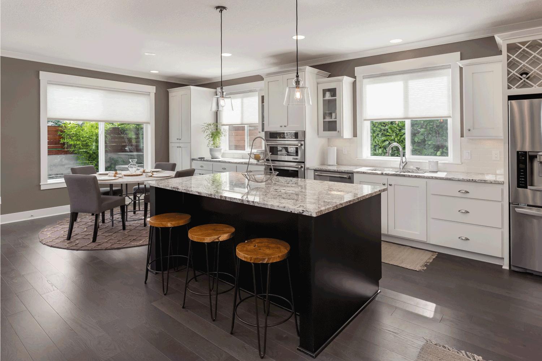 Beautiful kitchen in new luxury home with island, pendant lights, oven, range, and hardwood floors