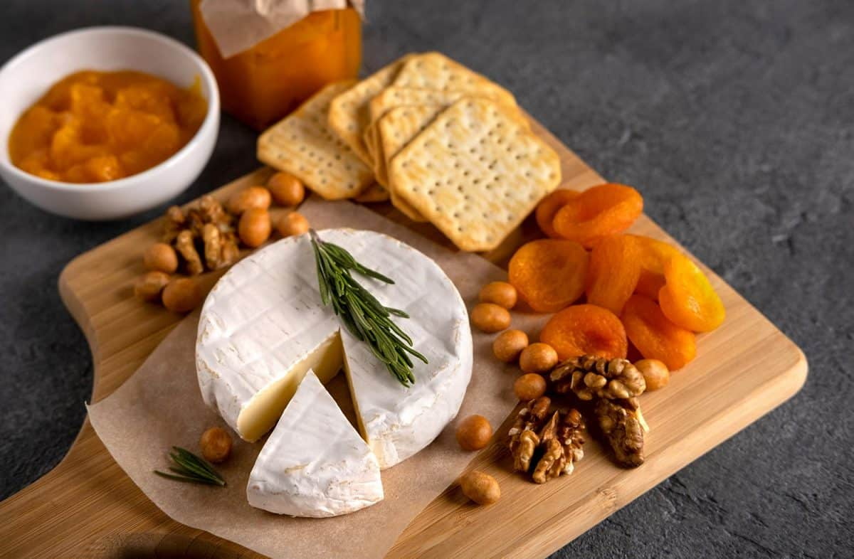 Brie cheese with nuts, pear slices and dried apricots