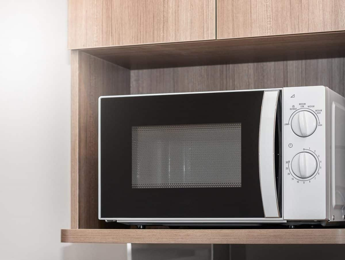 Close up of white microwave on a wooden shelf
