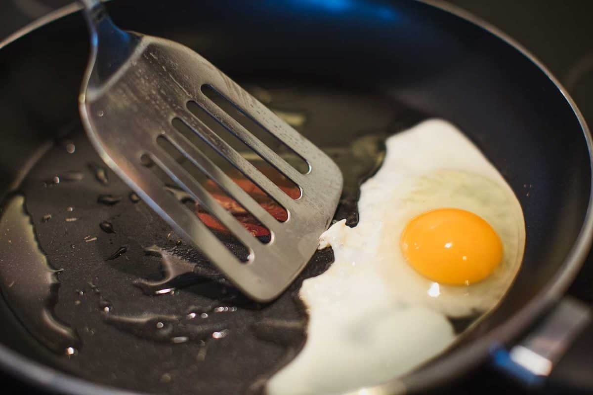 Close-up of an egg being fried going to be picked out with the spatula