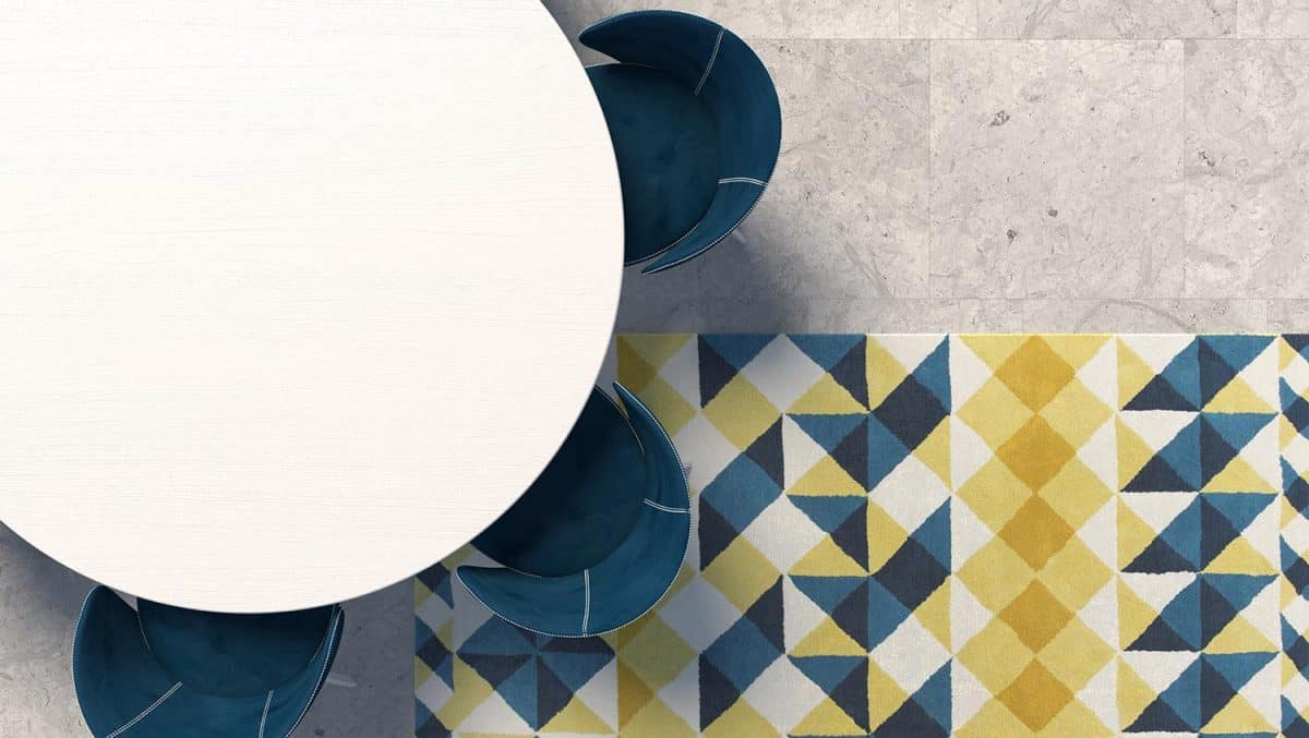 Empty white tabletop with blue armchair standing on the concrete floor with geometric patterned carpet
