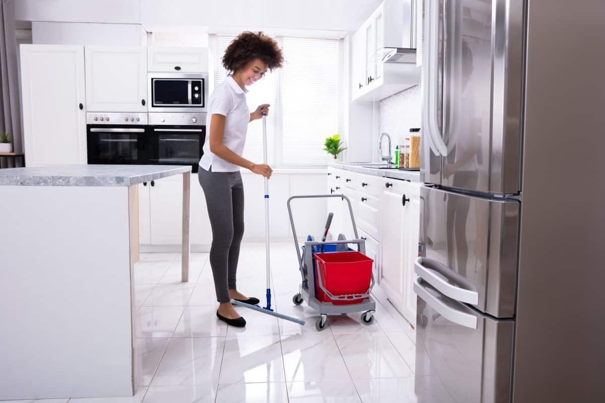 Female Janitor Cleaning The White Floor With Mop In Modern Kitchen