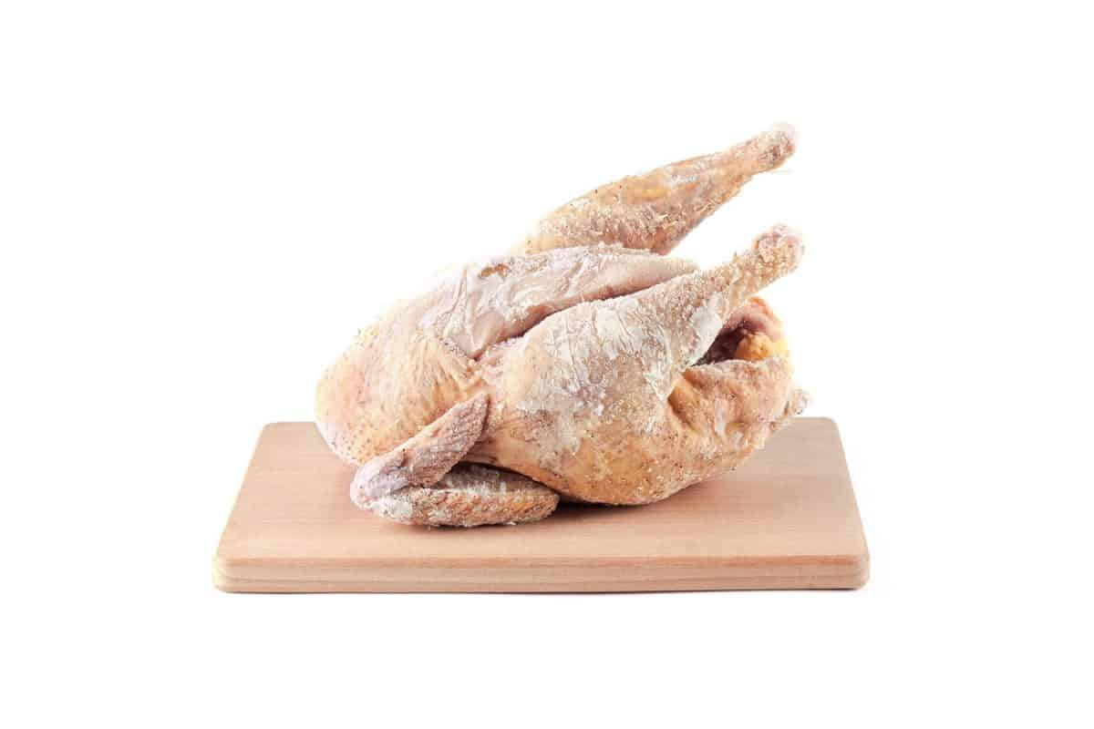 Frozen chicken carcass on a wooden chopping board