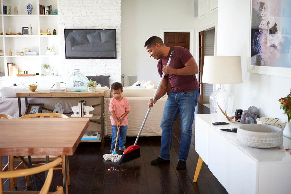 Grandfather and his three year old grandson mopping and sweeping the dining room floor