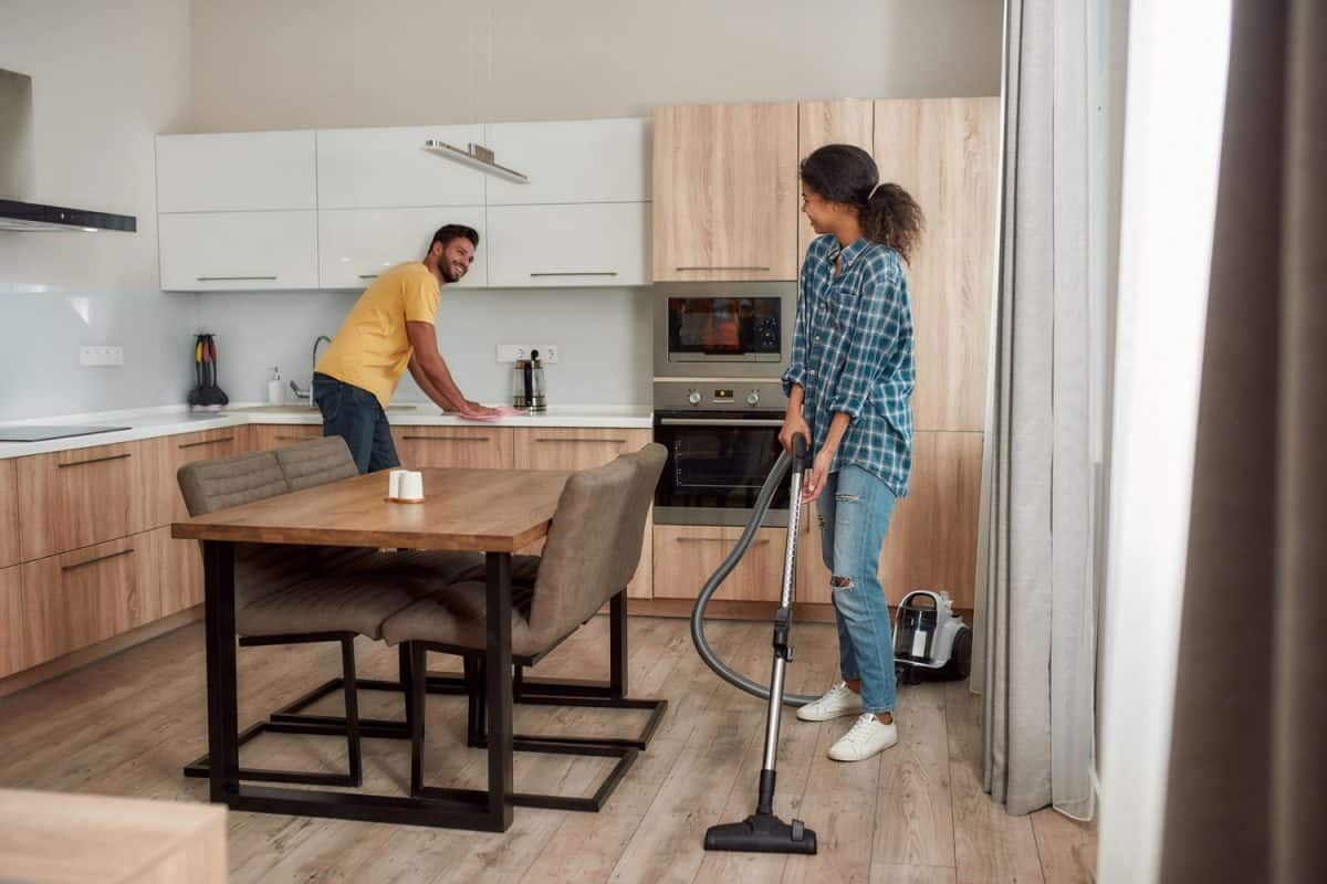 Happy multicultural couple in casual clothes cleaning their modern kitchen together, How To Make A Kitchen Floor Tile Look New