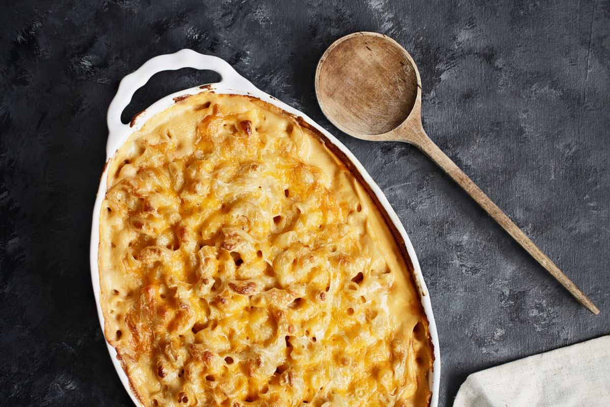 High angle view of a dish of fresh baked macaroni and cheese with table cloth and old wood spoon over a rustic dark background, Should You Cover Mac And Cheese When Baking?