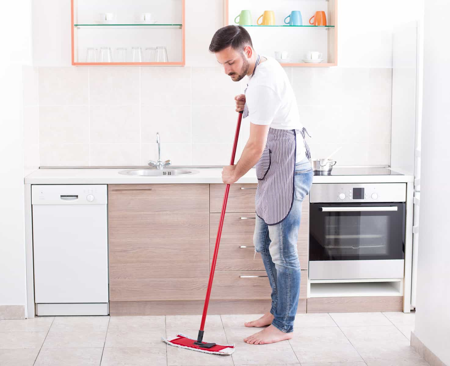 Young handsome man mopping tiled floor in kitchen. Husband housework concept