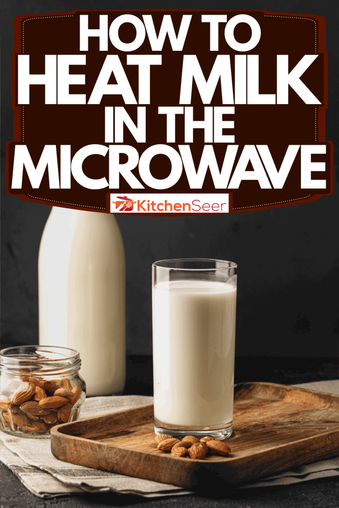 A glass of milk with almond nut on the small wooden coaster and a jar of milk on the background, How To Heat Milk In The Microwave