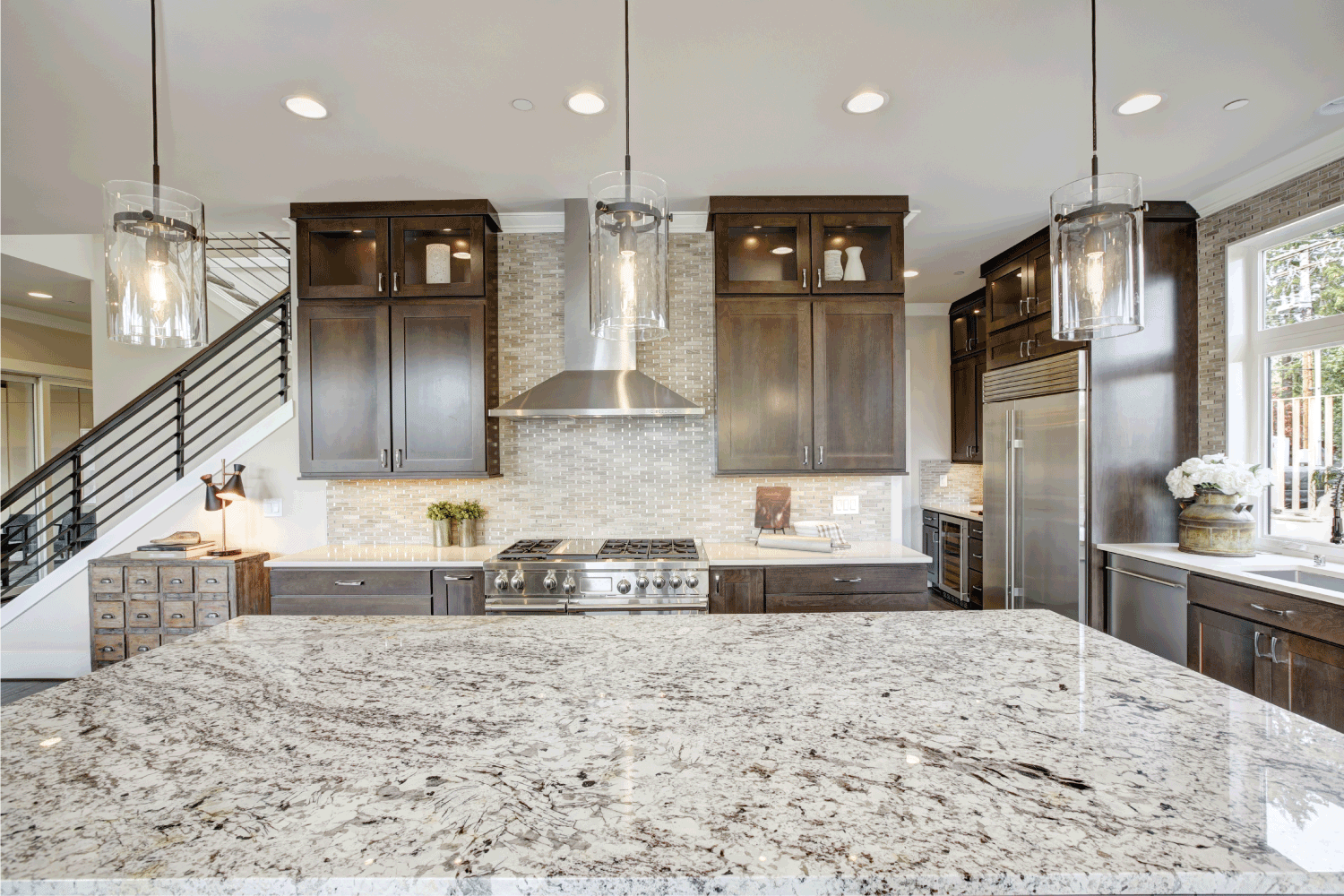 Luxury kitchen accented with large granite kitchen island, taupe tile backsplash, natural brown wood cabinets and lots of natural light