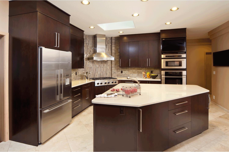 Modern kitchen with island and dark cabinets.