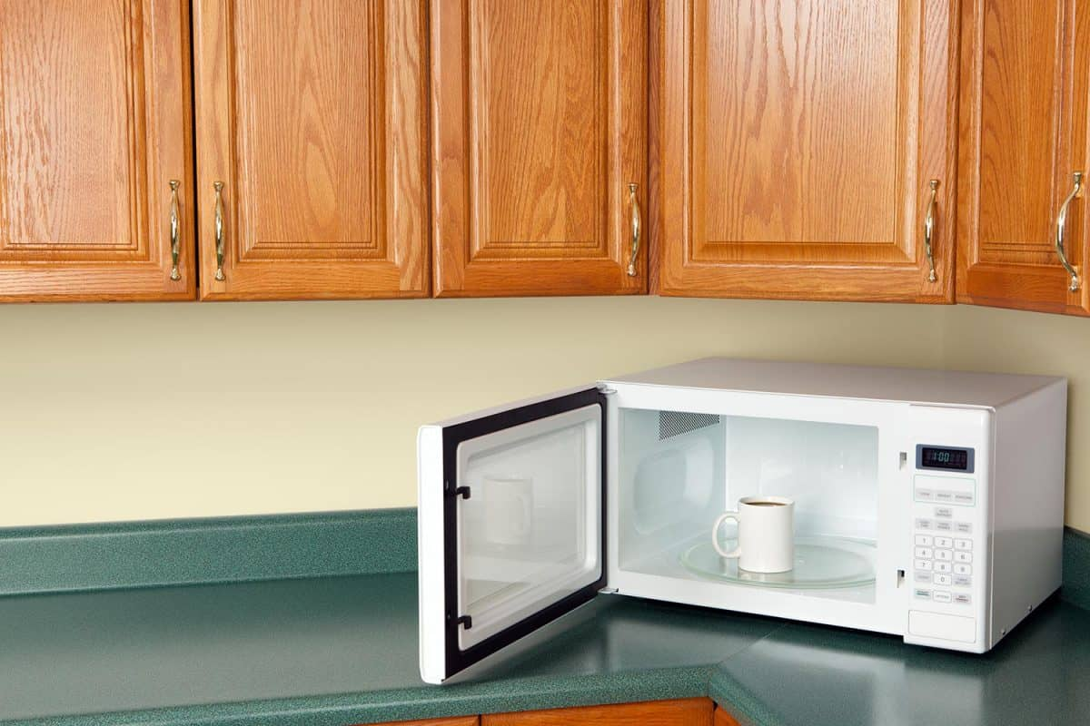 Open microwave oven on a kitchen counter with a cup of coffee inside