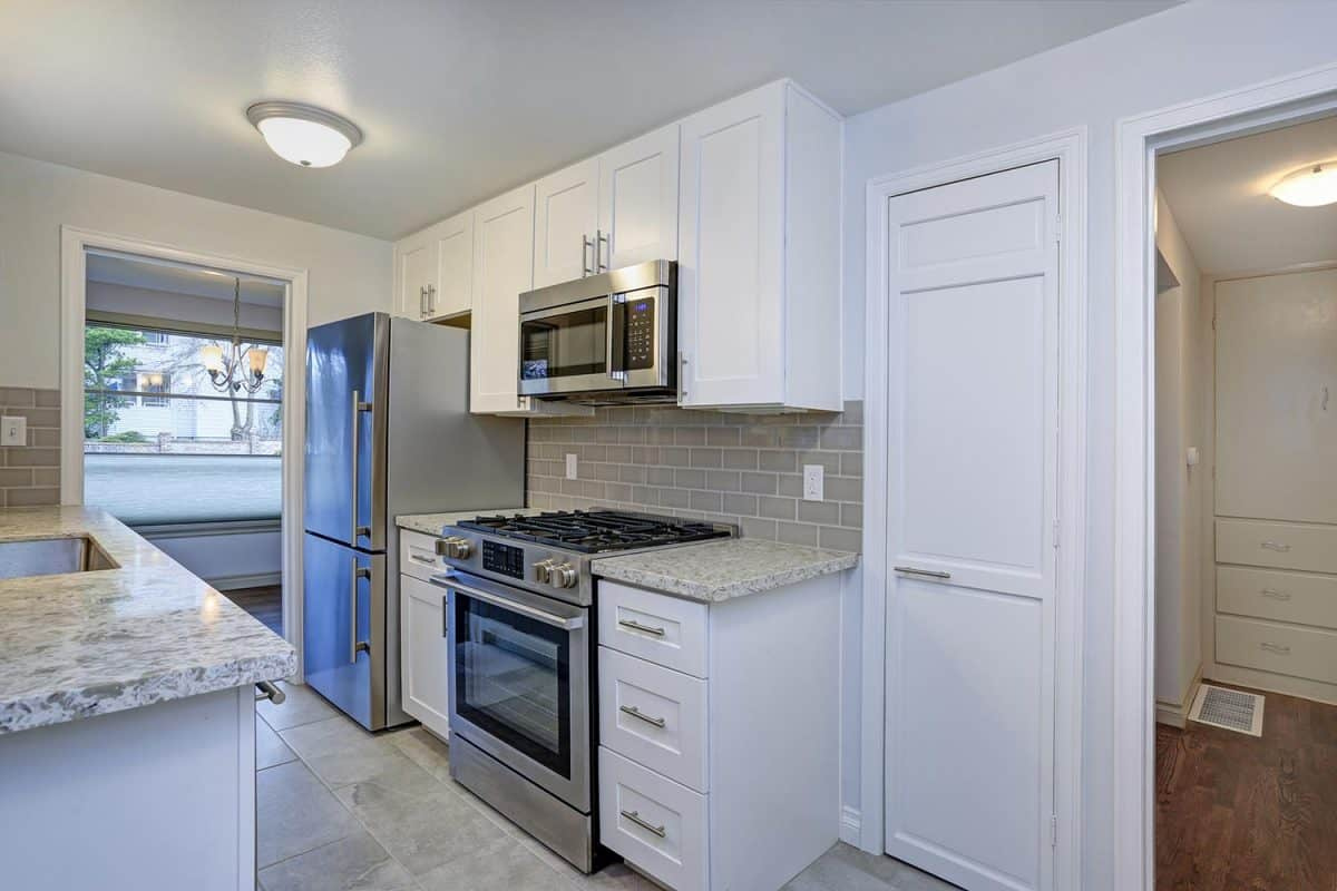 A small compact kitchen with white shaker cabinets