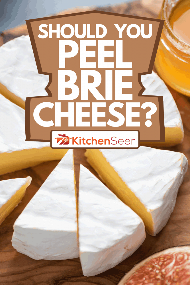 A brie cheese with grapes and honey on wooden serving board, Should You Peel Brie Cheese?