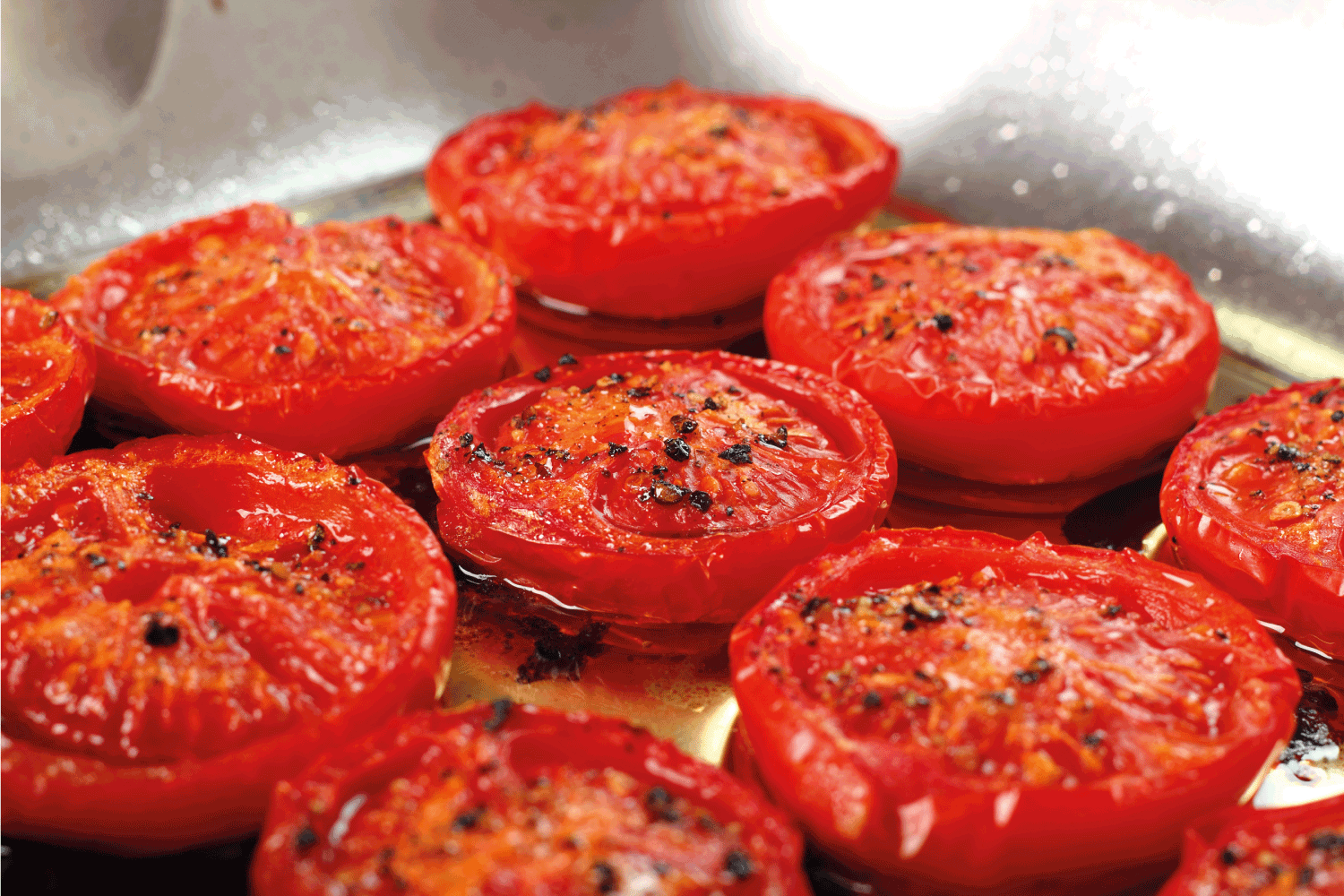 Slow Roasted Tomatoes in a stainless steel pan with olive oil