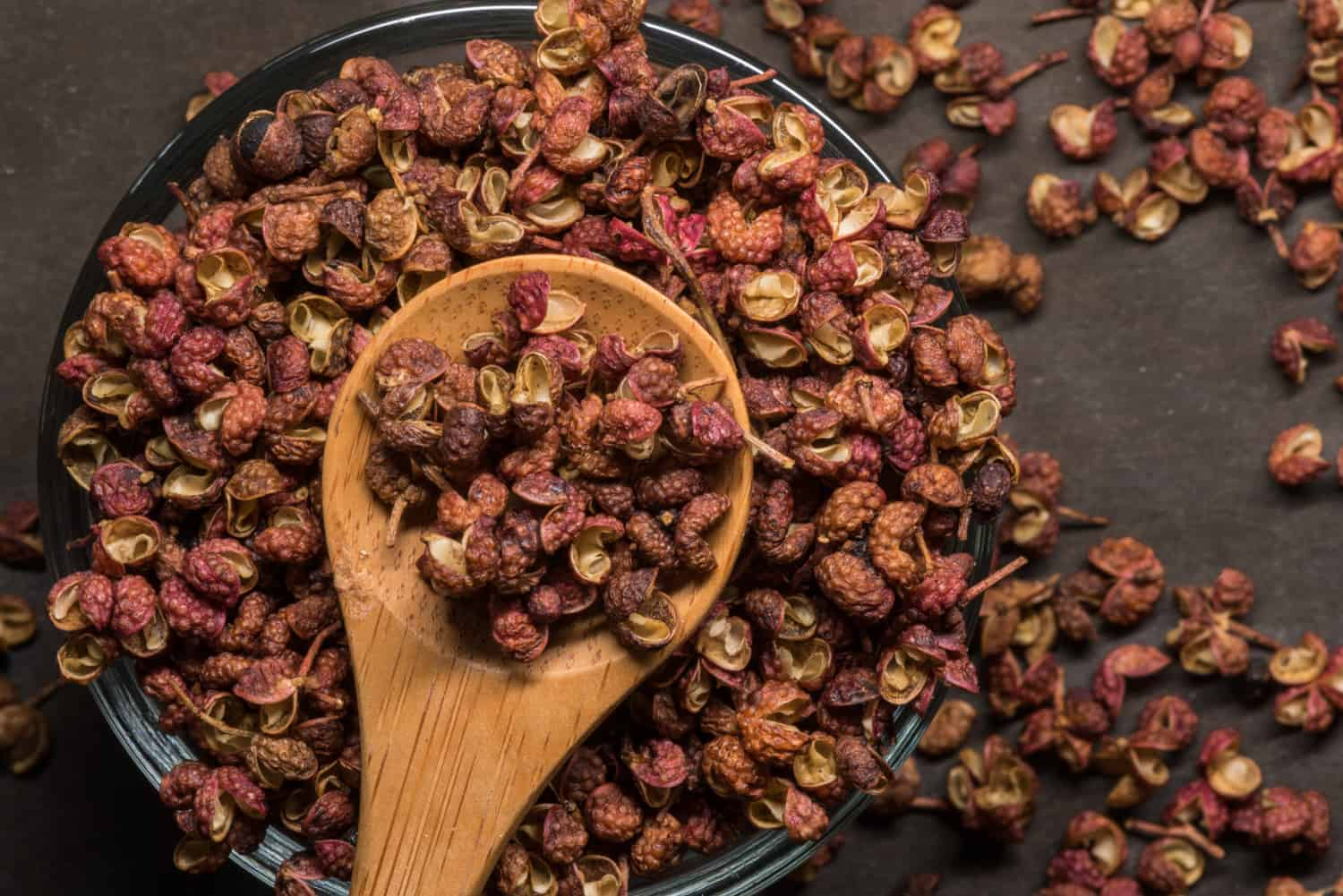 Szechuan Peppercorns in Wooden Spoon With Glass Bowl and spill over
