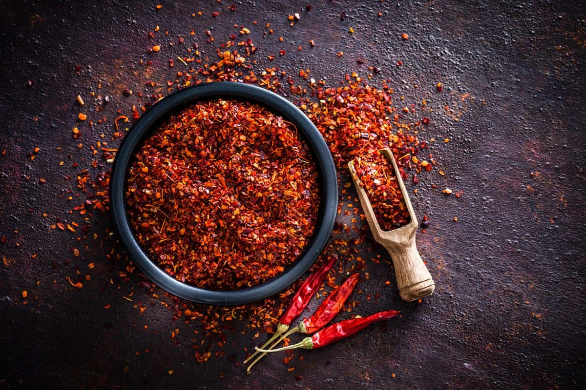 Top view of a black bowl filled with red chili pepper flakes shot on abstract brown rustic table.