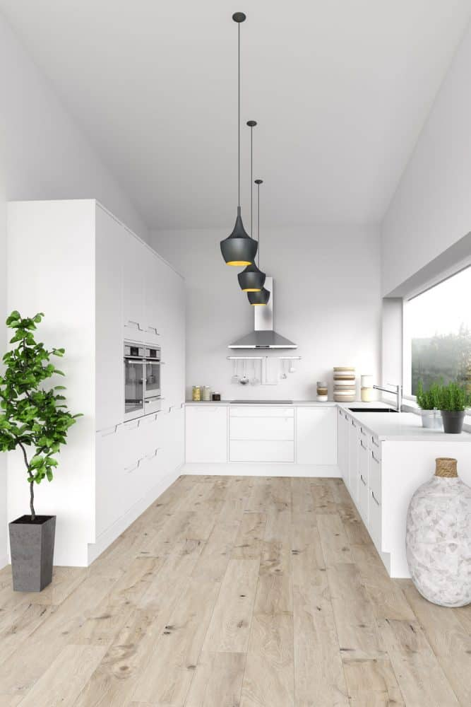 Ultra modern kitchen area with white walls, laminated flooring and black dangling lamps