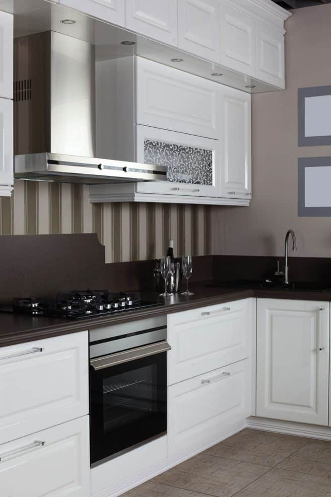 A black and white inpsired kitchen with white caibnets, stainless steel fixtures and a striped backsplash