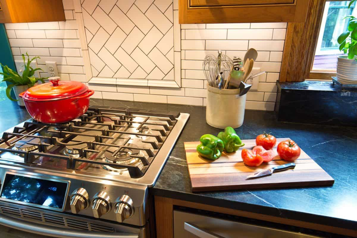 A classic styled kitchen with an orange dutch oven on the cooktop and bell peppers on the chopping board
