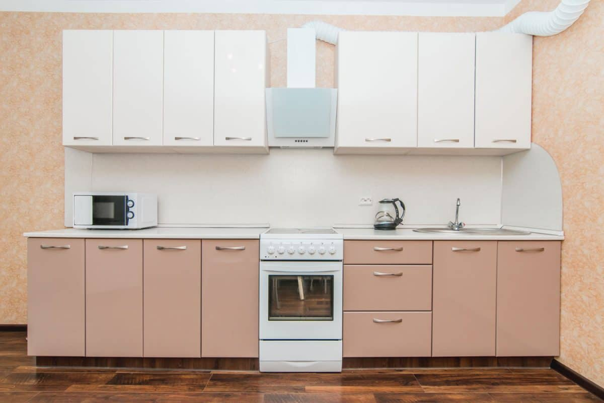 A light and small kitchen area with beige painted cabinets, white floating cabinets, and a white countertop