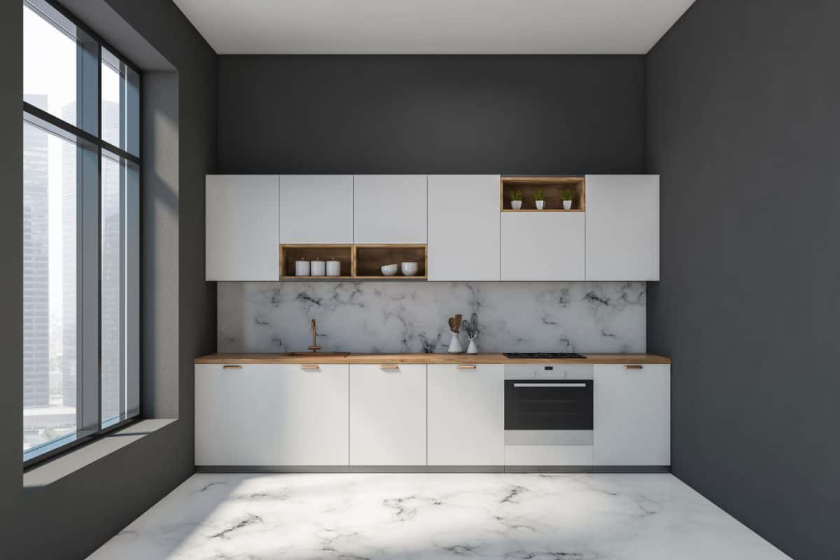 A narrow kitchen inside a condominium apartment with white painted kitchen cabinetry