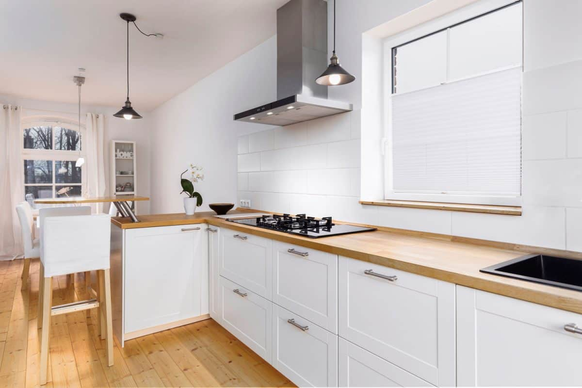 A rustic inspired kitchen with wooden countertop hardwood plank flooring and white painted cabinetry, Should Kitchen Countertops Match The Floor?