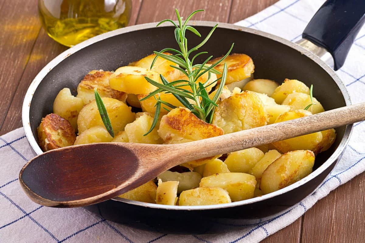 A skillet with oregano and roasted potatoes