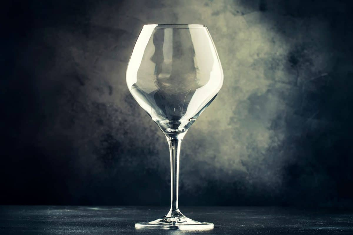A thick empty wine glass on a gray background