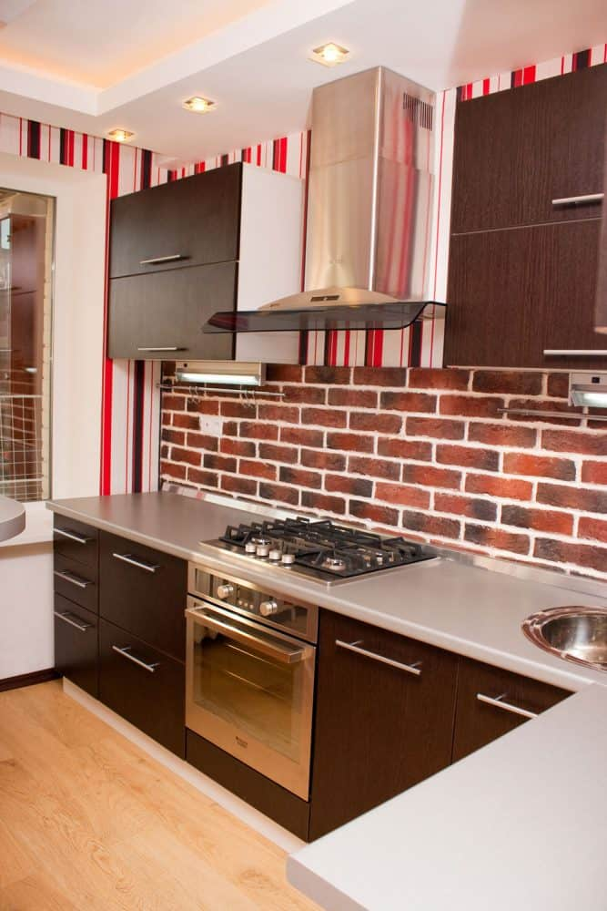 A white countertop inside a small kitchen with brown cabinets, brick wallpaper backsplash and a stainless steel range hood
