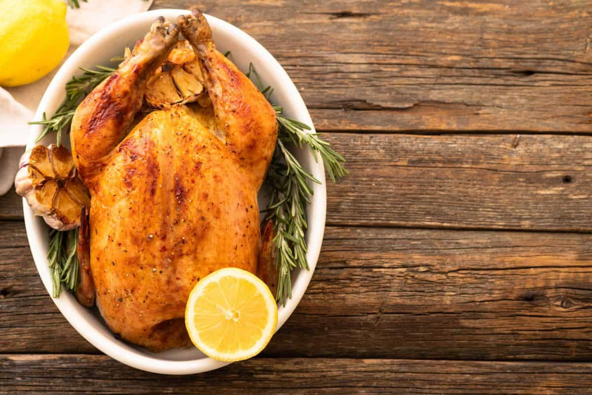 A hole baked chicken with oregano, sliced garlic and lime, At What Temperature Should You Bake Chicken?