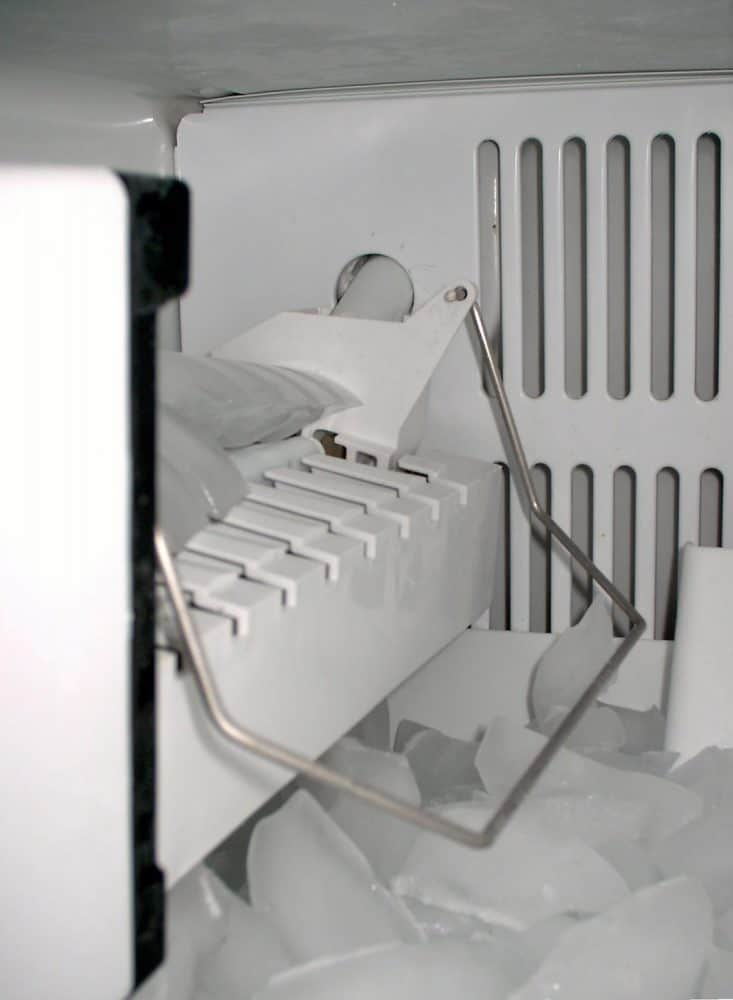 An automatic icemaker in the process of dumping ice cubes