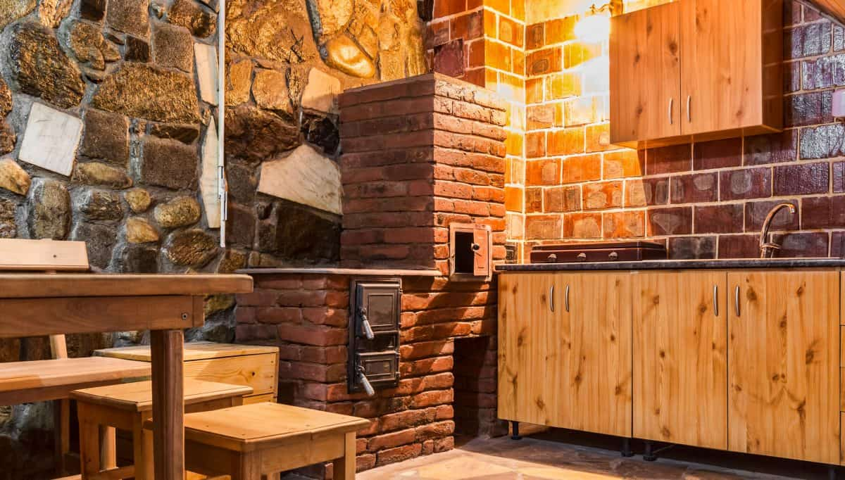 An extremely rustic inspired kitchen with decorative stones on the walls, a small brick oven, and wooden cabinetries and table