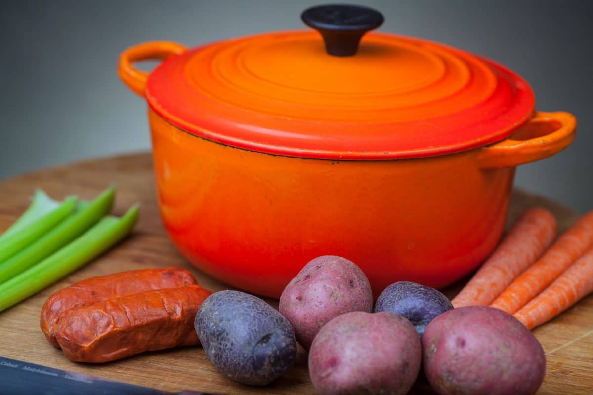 An orange Dutch oven with different root crops on the chopping board