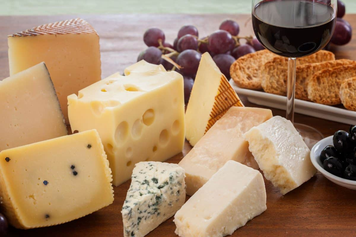Assorted cheeses (such as ementhal, blue cheese, pecorino, parmesan and manchego among others) served with bread, grapes, black olives and a glass of red wine on a wooden table, Should Cheese Be Served At Room Temperature?