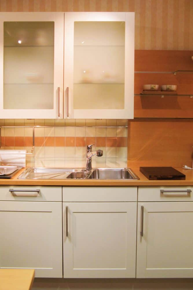 Classic designed kitchen with brown countertop, white kitchen cabinets and a small window opening