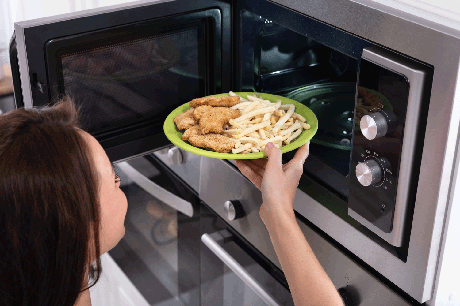 Close-up Of A Young Woman Heating Fried Food In Microwave Oven