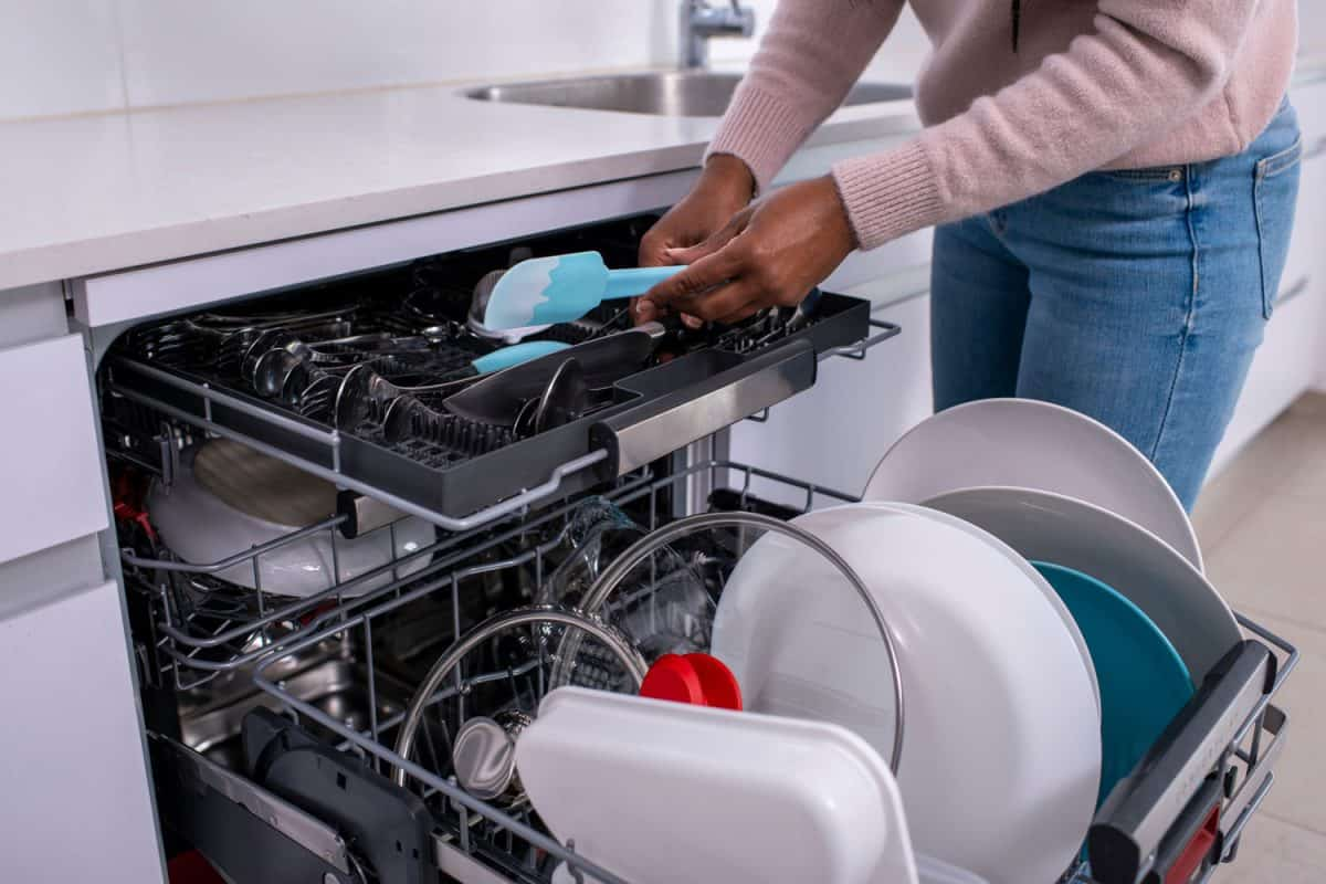 Close up image of a woman's hands holding a spatula, taking out clean cutlery from the dishwasher rack, Do Dishwashers Waste Or Save Water And Electricity?