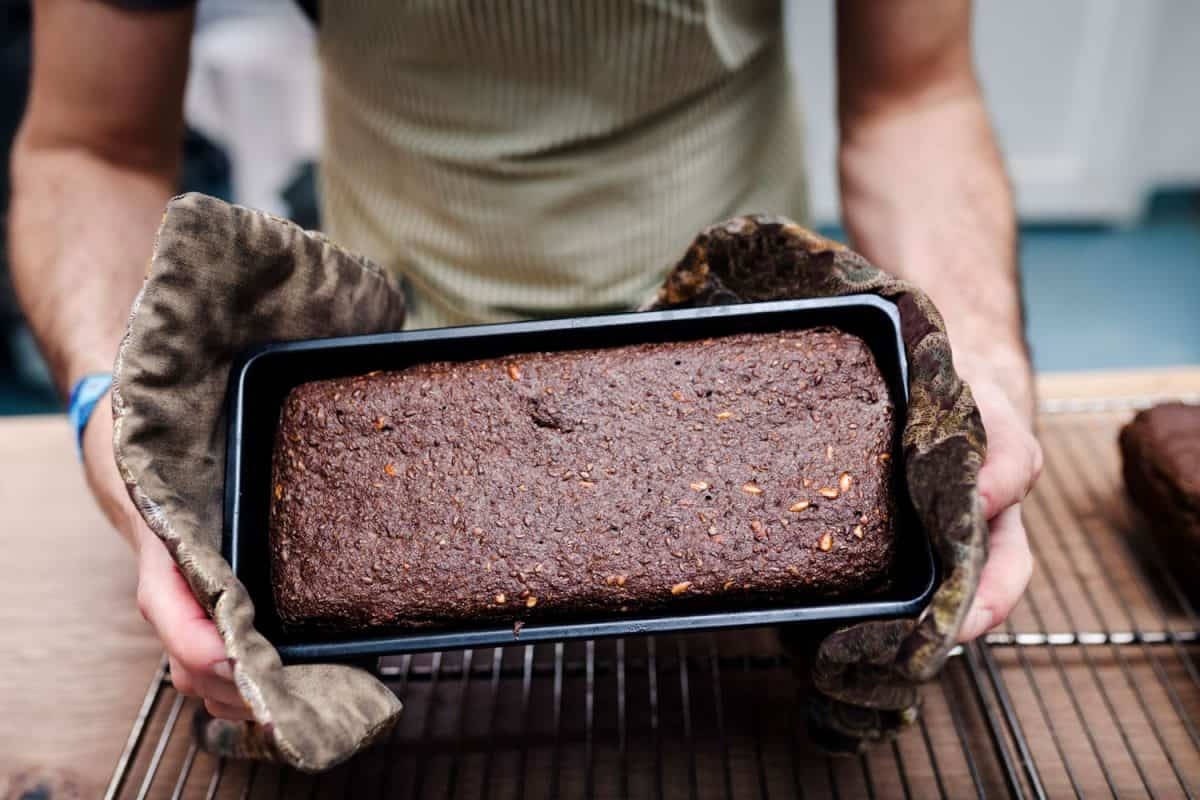 Close-up of a freshly baked loaf of rye bread as the baker shakes it out of it's loaf pan, How Full Should A Cake Pan Be?