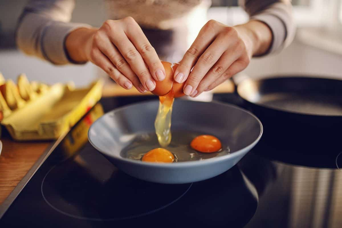 Close up of Caucasian woman breaking egg and making sunny side up