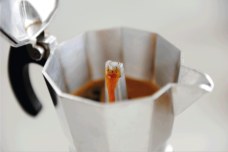 Coffee brewing in Italian espresso maker moka pot close up
