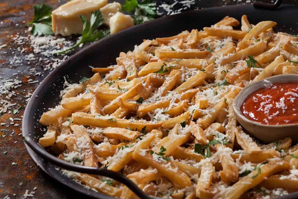 Crispy parmesan garlic Fries with fresh parsley and ketchup