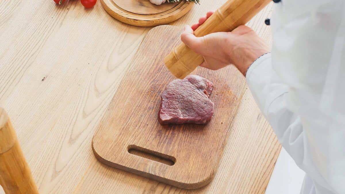 Cropped view of chef with mill seasoning beef steak on chopping board
