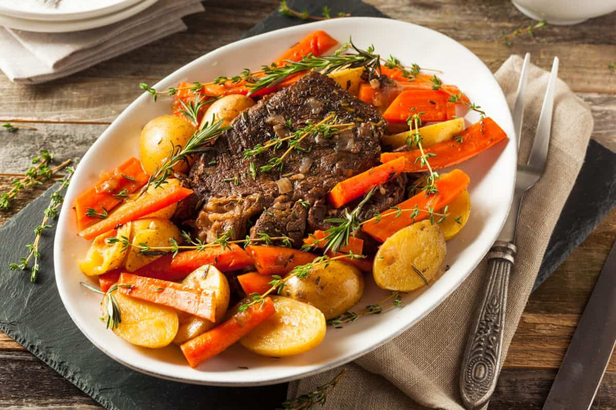 Delicious dish of pot roast with vegetables and potatoes garnished with oregano