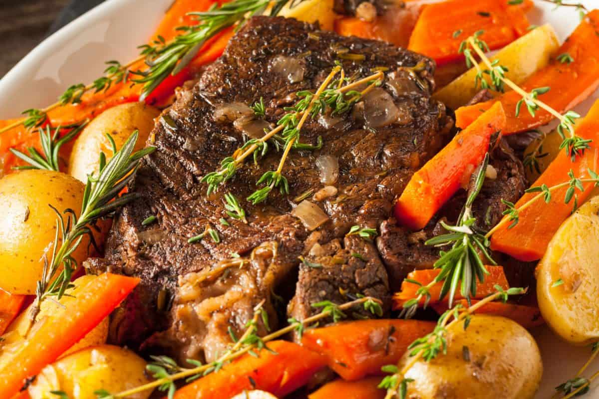 Delicious dish of pot roast with vegetables and potatoes garnished with oregano photographed up close, What Is The Best Cut Of Roast For Instant Pot?